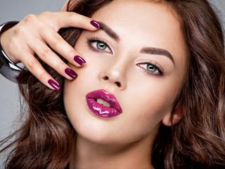 Foto op Plexiglas Beauty Beautiful and stunning woman with purple lipstick on lips and fingernails.