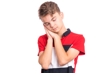 Fototapete - Portrait of teen boy sleeping tired or dreaming posing with hands together while smiling with closed eyes. Cute young caucasian teenager isolated on white background. Happy child.