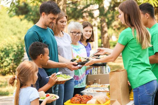 Young volunteers giving food to poor people outdoors