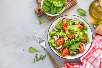 Green salad from fresh leaves and tomatoes.
