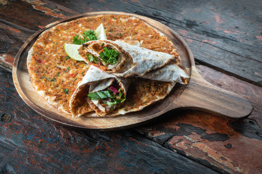 Lahmacun traditional Turkish pizza and wraps with salad isolated on rustic wooden table