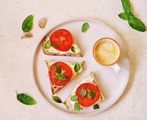 Open hot sandwiches with mozzarella cheese, fresh tomato and basil on a white plate on a light concrete background. Italian food. Top view, copy space.