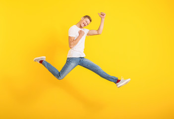 Jumping man in stylish t-shirt on color background