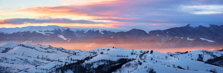 gorgeous panorama of mountainous countryside at sunrise in winter. snow covered rural area on rolling hills glow in morning sunlight. huge mountain ridge in a distance under cloudy sky