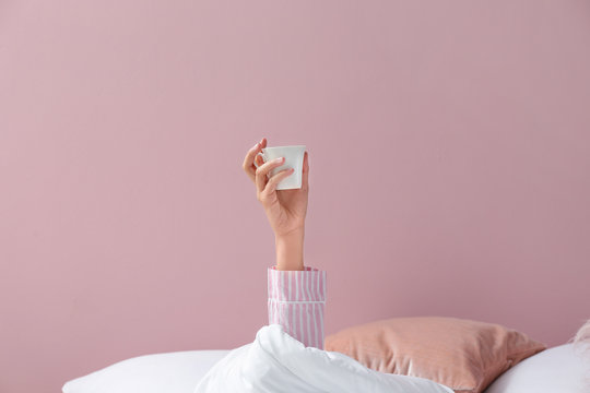 Young woman with cup of coffee lying in bed