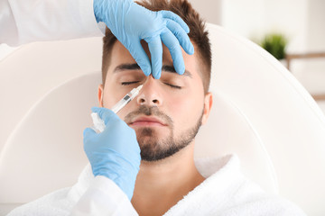 Handsome man receiving filler injection in beauty salon