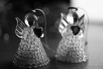 two small statues of angels on the table, bw photo.