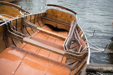 Small rowing boat moored on banks of Lake Windermere