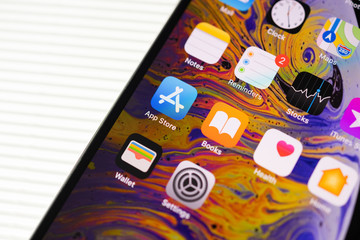 PARIS, FRANCE - SEP 27, 2018: new iPhone Xs Max  by Apple Computers close up with all home apps placed in 45 degrees on stripes white background - app store, books, reminders, stocks, maps clock apps