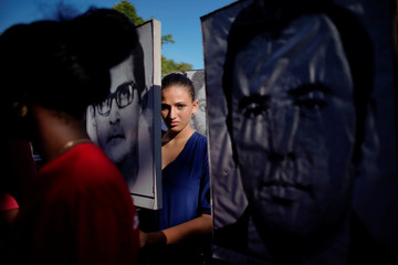 A girl peers through pictures of the 73 people killed in the 1976 downing of a Cuban airliner in Barbados while attending a memorial ceremony at the Colon cemetery in Havana