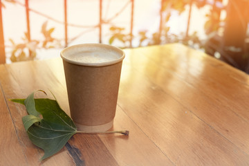 Paper coffee cup from coffee shop on wooden background