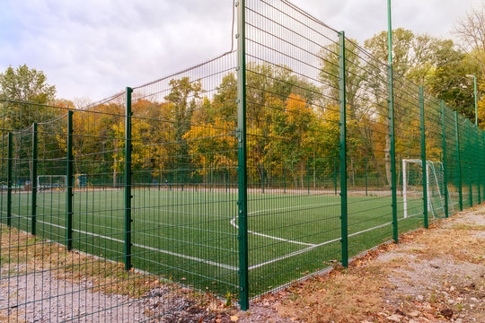 Mini-football court fenced with a green fence in autumn day