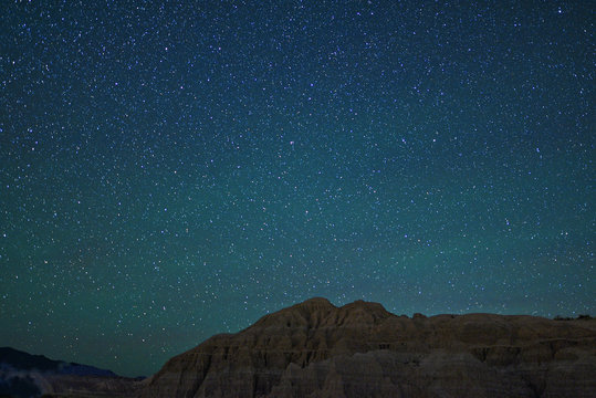 A starry sky over a desert mountain