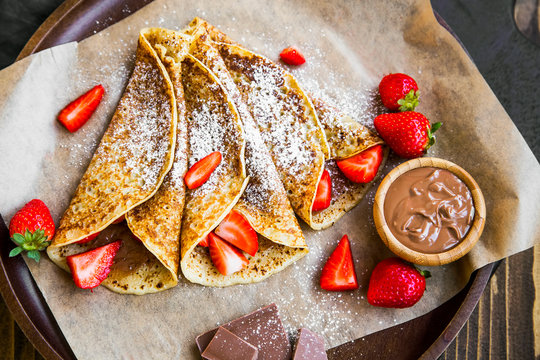 French crepes with chocolate spread and strawberries