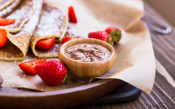Chocolate cream sauce with french crepes and fresh strawberries