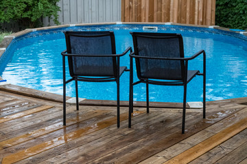 Two garden chairs on the wooden deck in front of the pool