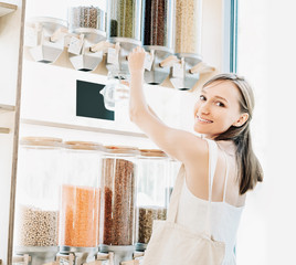 Zero waste shop. Girl buying in sustainable plastic free grocery store.