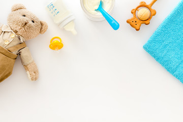 Baby food background with toys and accessories on white table top view pattern frame copy space