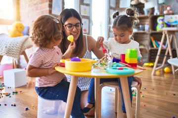 Young beautiful teacher and toddlers playing meals using plastic food and cutlery toy at kindergarten