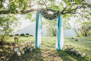 Sunset wedding ceremony arch with flower decoration and blue cloth canopy hanging on big tree. Blue hydrangea, pink roses, lily. Pastel colored.