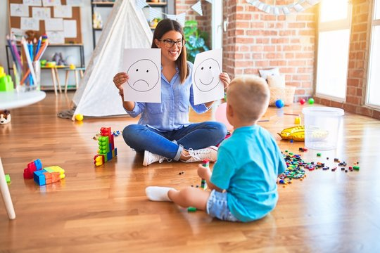 Young therapist woman speaking with child, counselor and behaviour correction at the office showing happy and sad face