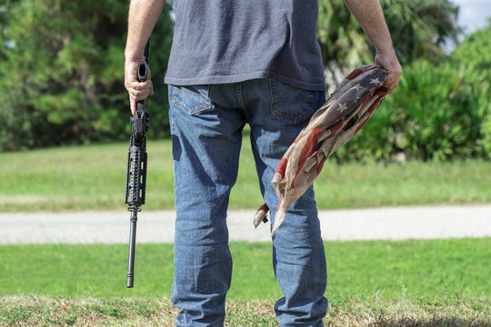 Conservative Caucasian Man Holding AR-15 Automatic Assault Rifle And American Flag Under Constitution 2nd Amendment