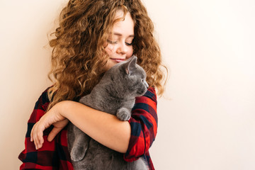 Curly blond teenage girl smiles and holds in her hands a gray kitten of Scottish breed. In a red...