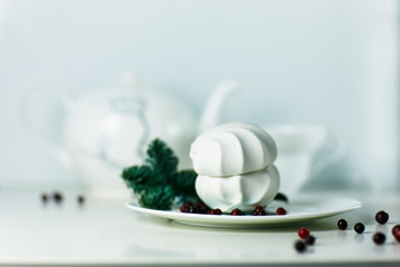 White marshmallow and green xmas tree branch with berry