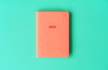 Orange diary for 2020 with artificial leather cover on a mint background. New Year concept in trendy colors