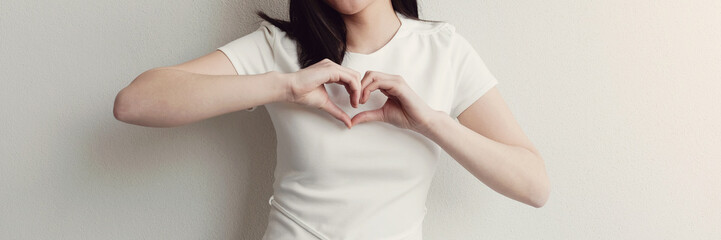 Happy Asian young woman making her hands in heart shape, hope, heart health insurance, social...
