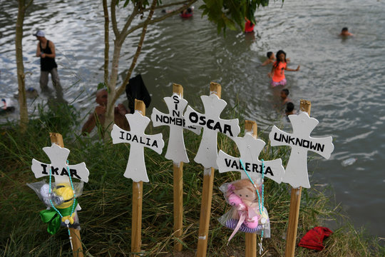 """Crosses honoring the lives of migrants who've died on their journeys north are pictured as migrants bathe in the Rio Grande near a makeshift encampment occupied by asylum seekers, most of whom were sent back to Mexico from the U.S. under the """"Remain in Mex"""