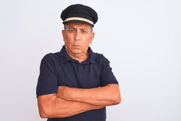 Senior grey-haired man wearing black polo and captain hat over isolated white background skeptic and nervous, disapproving expression on face with crossed arms. Negative person.
