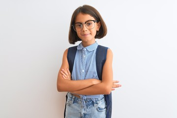 Beautiful student child girl wearing backpack and glasses over isolated white background happy face smiling with crossed arms looking at the camera. Positive person.