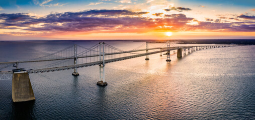 Poster Bruggen Aerial panorama of Chesapeake Bay Bridge at sunset. The Chesapeake Bay Bridge (known locally as the Bay Bridge) is a major dual-span bridge in the U.S. state of Maryland.