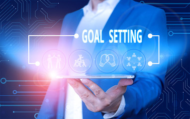 Text sign showing Goal Setting. Business photo text process of identifying something that you want to accomplish Male human wear formal work suit presenting presentation using smart device