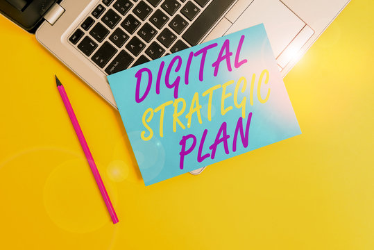 Conceptual hand writing showing Digital Strategic Plan. Concept meaning creat schedule for marketing product or brand Metallic laptop small paper sheet pencil colored background