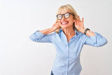 Middle age businesswoman wearing elegant shirt and glasses over isolated white background Trying to hear both hands on ear gesture, curious for gossip. Hearing problem, deaf
