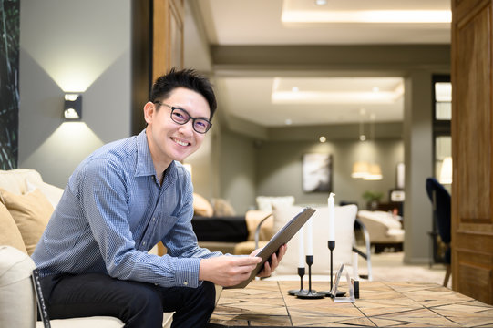 Asian man real estate agent hands holding clipboard document sitting on sofa in example house