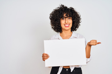 Young arab woman with curly hair holding banner over isolated white background pointing and showing...