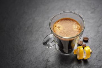 Fotorollo Kaffee Espresso coffee mug with lemon peel on black background