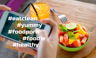 hand with mobile phone screen taking picture of fruit salad and juice for in internet social media blog in healthy nutrition lifestyle composed with foodie hashtags