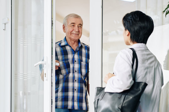 Smiling senior man in plaid shirt opening glass door to invite caregiver to house