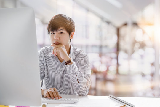 Cropped shot of a serious asian businessman thinking and concentrating typing on laptop at co-working spaces. Man laptop working concept