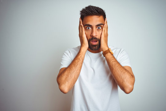 Young indian man wearing t-shirt standing over isolated white background afraid and shocked, surprise and amazed expression with hands on face