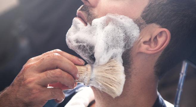 Hairdresser applying cream for shaving.