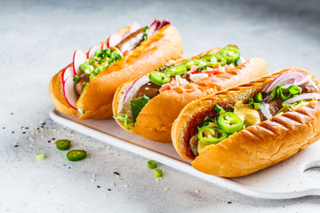 Hot dogs with different toppings on white background. Fast food concept.
