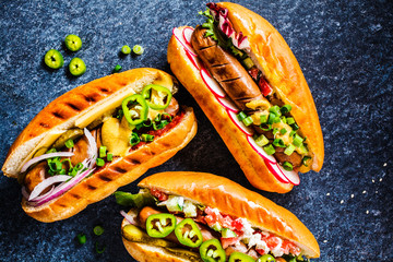Hot dogs with different toppings on dark blue background, top view. Fast food concept.