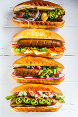 Hot dogs with different toppings on white wooden background, top view. Fast food concept.