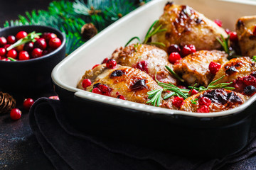 Christmas food. Baked Chicken meat with cranberries and rosemary in the oven dish, dark background.