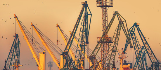Sunset over industrial cranes at commercial sea port of the city of Varna, Bulgaria.image